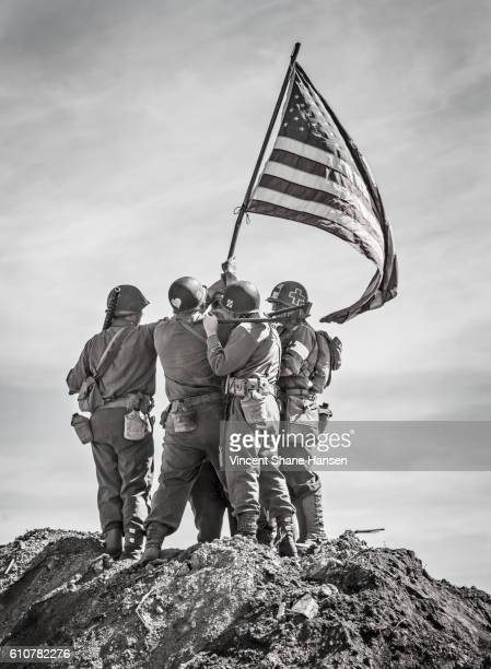 soldiers raising the us flag - armistice day stock photos and pictures
