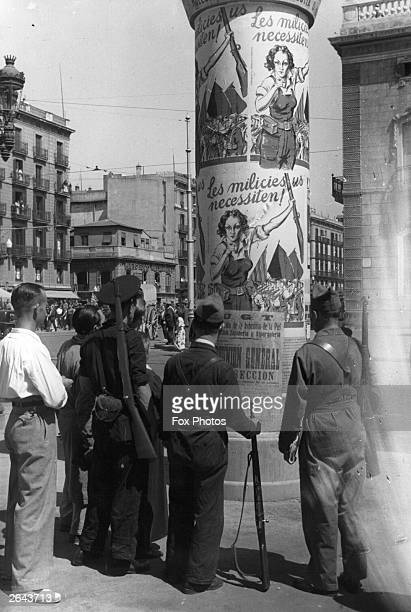 Soldiers read posters in Barcelona calling women to arms during the Spanish Civil War