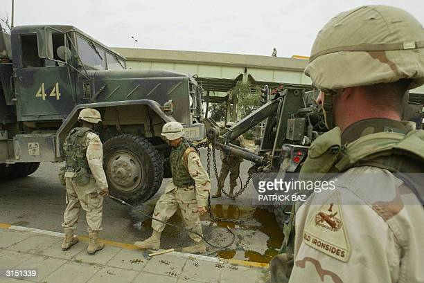 US soldiers remove a truck lightly damaged by an improvised explosive device that exploded 29 March 2004 in eastern Baghdad The device was placed...