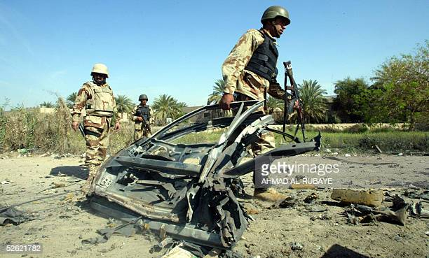 US soldiers remove debris from the scene of a roadside bombing in the Baghdad district of Amariya considered a haven for rebels 13 April 2005 A car...