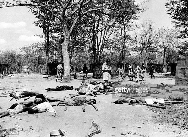 Soldiers remove the bodies in a mass grave which will be set on fire to prevent disease after a savage revenge raid by Senga villagers on members of...