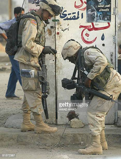 US soldiers removes a detonator leading to an improvised explosive device from a main road in the poor neighborhood of Sadr City in Baghdad 25...