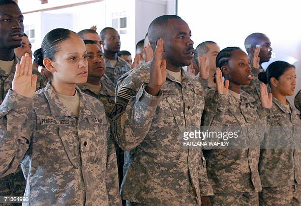 Soldiers representing 17 countries of origin including one from Afghanistan raise their hands as they take the oath during a naturalization ceremony...