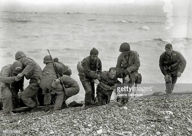 Two US soldiers rescue others from the sea in front of Omaha Beach 6th June 1944 Many soldiers drowned because they had not inflated their life...