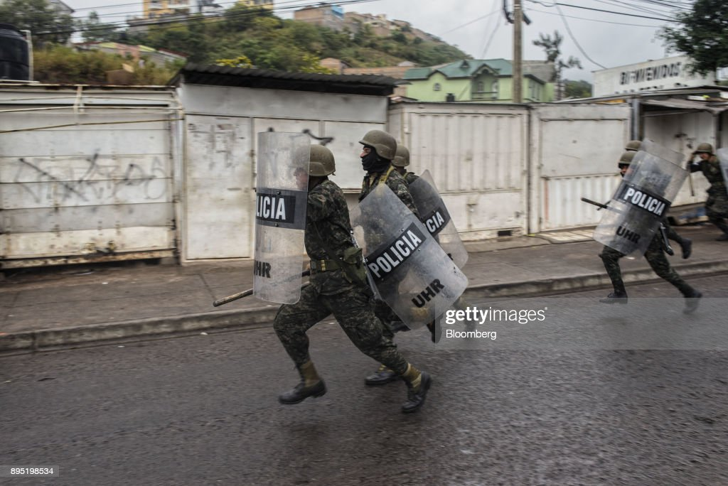 Soldiers run as they pursue protesters during protests against the presidential election of Juan Orlando Hernandez in Tegucigalpa, Honduras, on Monday, Dec. 18, 2017. Honduran electoral authorities declared incumbent Hernandez the winner of the Nov. 26 presidential vote after three weeks in which the nation slid into chaos as ballots were counted and recounted. Photographer: Juan Carlos/Bloomberg via Getty Images