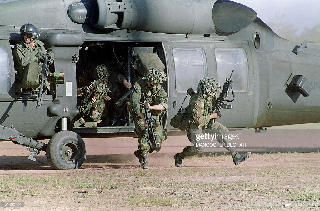 U.S. soldiers run for cover following their arrival at a military command post loyal to General Manuel Antonio Noriega 23 December 1989 in Santiago 200 miles north of the capital.