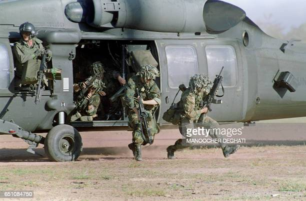 US soldiers run for cover following their arrival at a military command post loyal to General Manuel Antonio Noriega 23 December 1989 in Santiago 200...