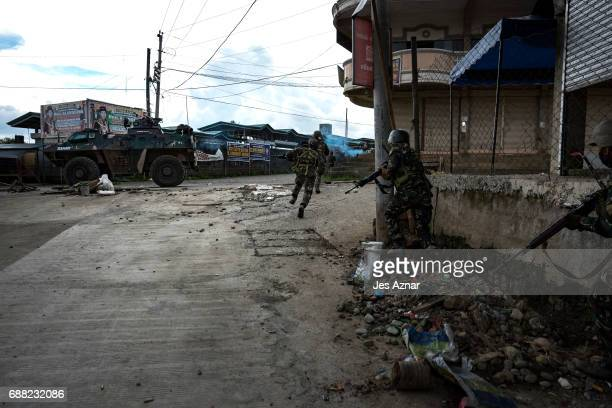 Soldiers run for cover to evade sniper fire while trying to clear the city of armed militants one street at a time on May 25 2017 in Marawi city...