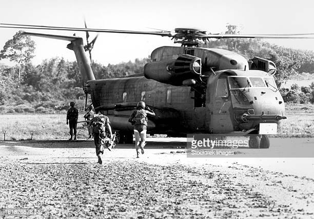 soldiers run to a hh-53c helicopter during an asualt on koh tang island. - helicopter photos stock pictures, royalty-free photos & images