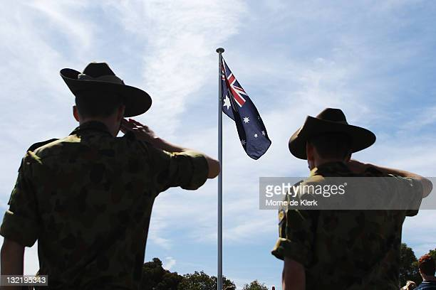 Soldiers salute as the Australian flag flies as part of today's Remembrance Day Commemorations at on November 11 2011 in Adelaide Australia One...