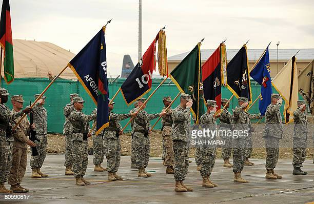 Soldiers salute during a ceremony held for the change of command between two US military contingents at Bagram air base, 50 kms north of Kabul on...