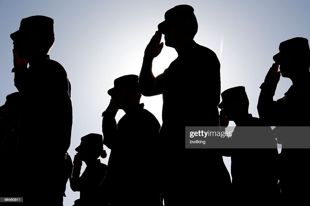 Soldiers Salute the Flag at Sunset : Stock Photo