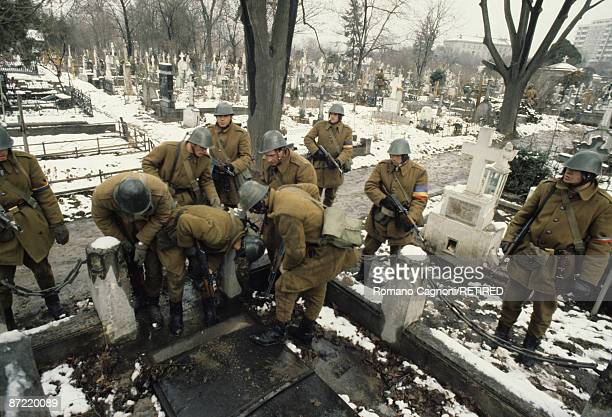 Soldiers search amongst the tombs of the cemetery in Bucharest for fugitives of the Ceausescu regime during the Romanian Revolution December 1989