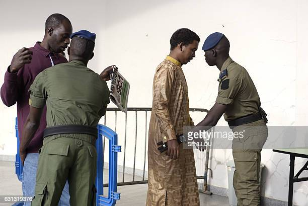 Soldiers search men outside a courtroom at Dakar courthouse on January 9 2017 on the first day of the former Chadian dictator Hissene Habre appeal...