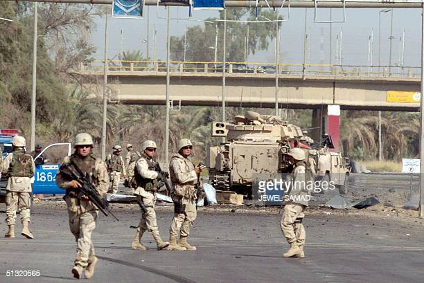 US soldiers secure the area 18 September 2004 near Baghdad's International Airport A US convoy was hit by a roadside bomb on the main highway to the...