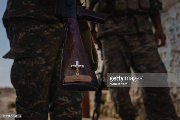 Soldiers show off religious decorations on their rifles at an outpost against attack from Azerbaijan outside of Martakert, Nagorno-Karabakh, which is...