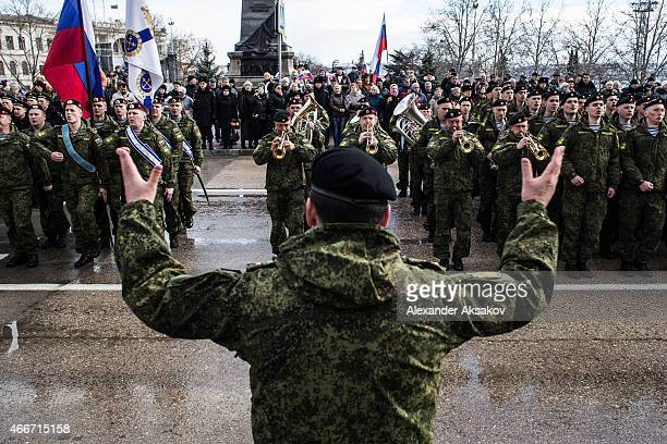 Soldiers sing songs in Nakhimova Square as people celebrate the first anniversary of the signing of the decree on the annexation of the Crimea by the...