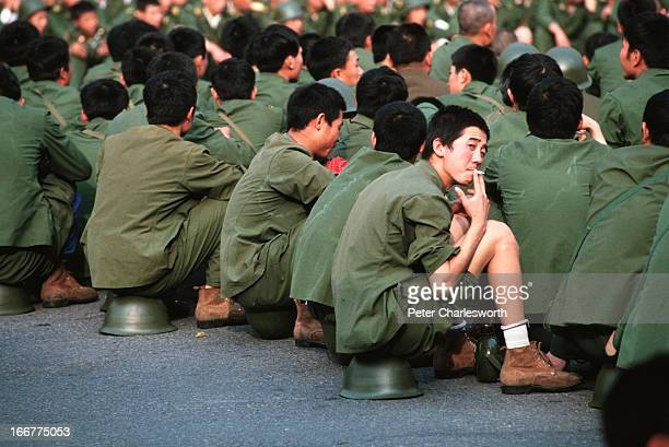 Soldiers sit around waiting because they have been prevented from entering Tiananmen Square by a huge crowd of prodemocracy demonstrators This was...
