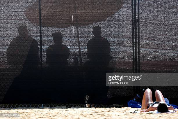 Soldiers sit on the other side of a temporary security barrier as a woman sunbathes on the unrestricted part of the beach during the AsiaPacific...
