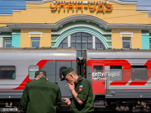 Soldiers smoke during a station stop on the TransSiberian Railway from MoscowVladivostok Spanning a length of 9289km it's the longest uninterrupted...