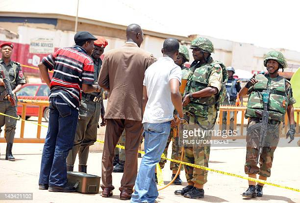 Soldiers speak with people wanting to cross the cordonnedoff roads leading to the premises of ThisDay Newspapers bombed in Abuja on April 26 2012 One...