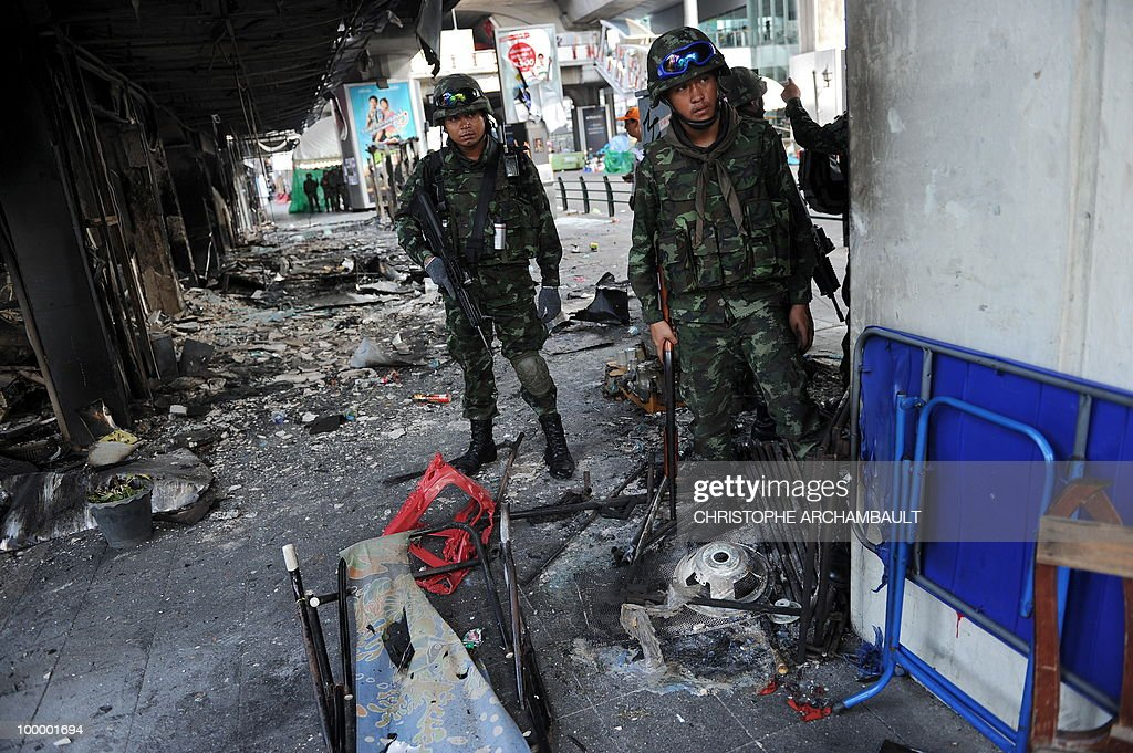 Soldiers stand alert by burnt shops after gunshots rang out near a Buddhist temple in the heart of an anti-government protest zone, in downtown Bangkok on May 20, 2010. Gunshots rang out near a Buddhist temple in the heart of an anti-government protest zone in Bangkok, and soldiers were advancing on foot along an elevated train track, an AFP photographer saw. Thai security forces stormed the 'Red Shirts' protest camp on May 19 in a bloody assault that forced the surrender of the movement's leaders who asked their supporters to disperse. AFP PHOTO/Christophe ARCHAMBAULT