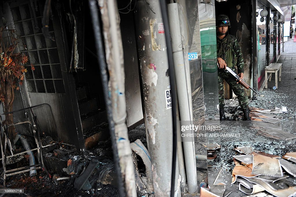 Soldiers stand alert by burnt shops after gunshots were heard near a Buddhist temple in the heart of an anti-government protest zone, in downtown Bangkok on May 20, 2010. Gunshots rang out near a Buddhist temple in the heart of an anti-government protest zone in Bangkok, and soldiers were advancing on foot along an elevated train track, an AFP photographer saw. Thai security forces stormed the 'Red Shirts' protest camp on May 19 in a bloody assault that forced the surrender of the movement's leaders who asked their supporters to disperse. AFP PHOTO/Christophe ARCHAMBAULT