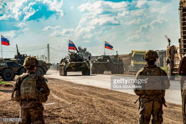 Soldiers stand along a road across from Russian military armoured personnel carriers , near the village of Tannuriyah in the countryside east of...