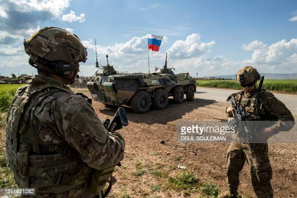 Soldiers stand along the side of a road across near a Russian military armoured personnel carrier , near the village of Tannuriyah in the countryside...