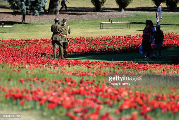 Soldiers stand amoungst a field of fabric poppies ahead of the Remembrance Day Service at the Australian War Memorial on November 11 2018 in Canberra...