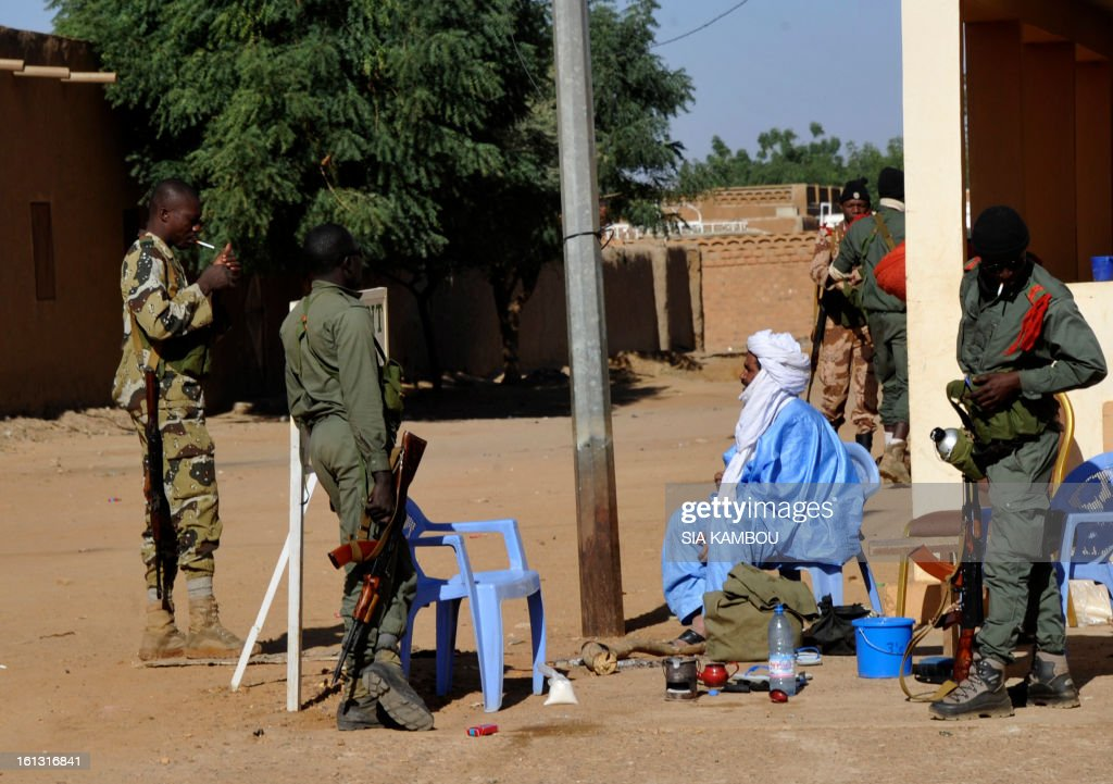 Soldiers stand around a seated Toureg aprehended on February 7, 2013 during reinforced security patrols of Gao. A massive explosion was heard near Gao in northern Mali late Saturday, hours after villagers near the city detained two youths preparing for suicide bombings.