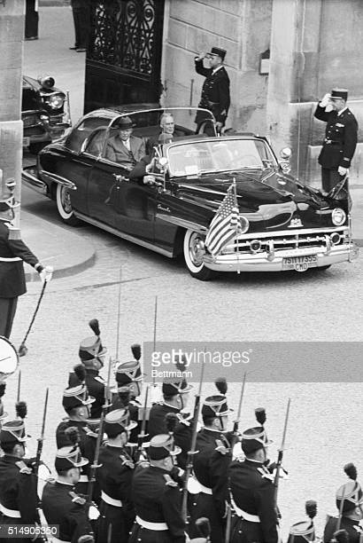 Soldiers stand at attention and salute as United States President Eisenhower and Secretary of State Christian Herter arrive by automobile at the...