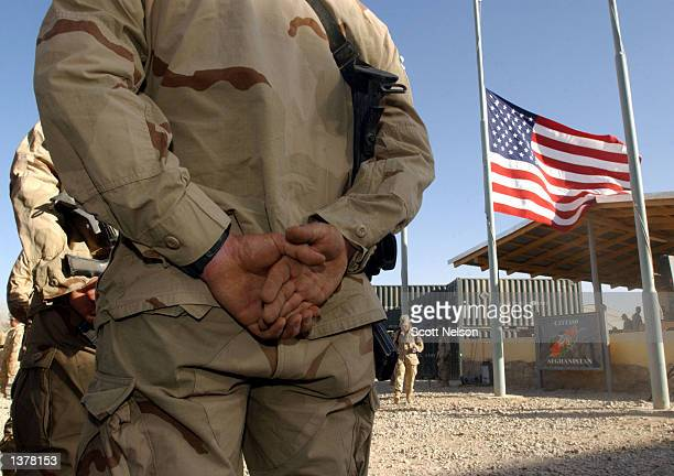 S soldiers stand at attention in front of an American flag at half staff on the first anniversary of the terrorist attacks on New York and the...