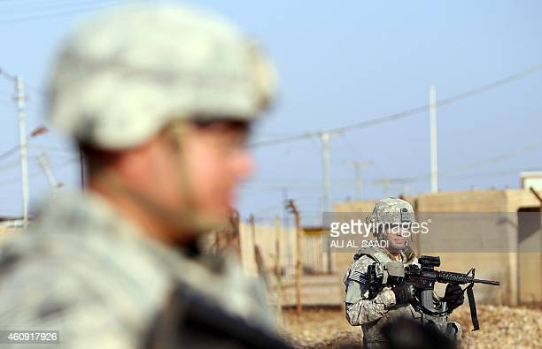 US soldiers stand at the Taji base complex which hosts Iraqi and US troops and is located thirty kilometres north of the capital Baghdad on December...