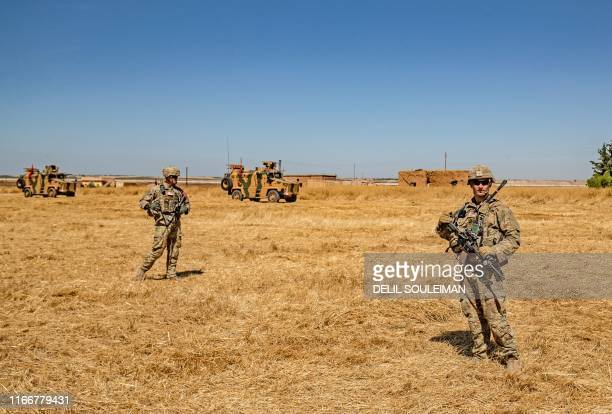 US soldiers stand close to Turkish military vehicles during a joint patrol with Turkey in the Syrian village of alHashisha on the outskirts of Tal...