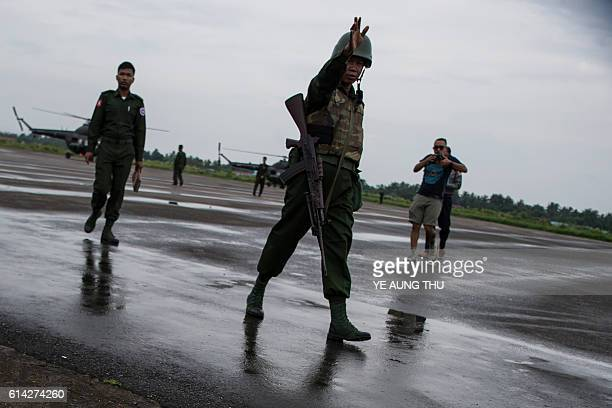 Soldiers stand guard as Myanmar air force helicopters arrive at Sittwe airport in Sittwe capital of Rakhine State on October 13 with troops pouring...
