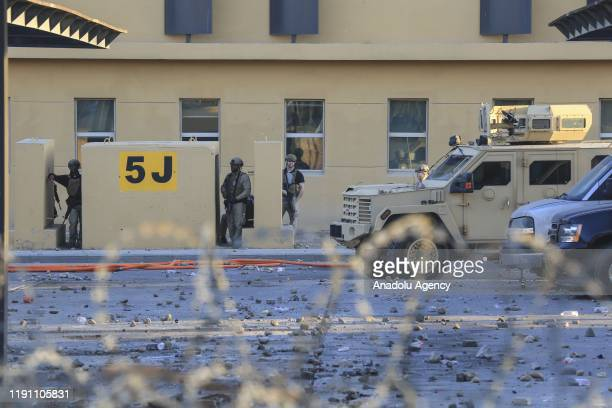 US soldiers stand guard as outraged Iraqi protesters storm the US Embassy in Baghdad protesting Washington's attacks on armed battalions belong to...