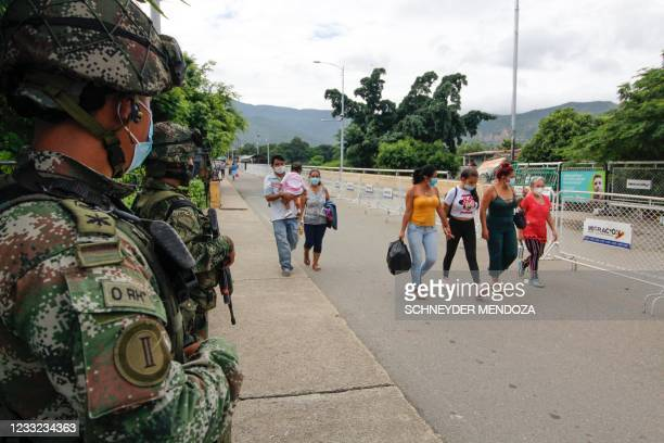 Soldiers stand guard as people cross the Simon Bolivar International Bridge from Venezuela into Cucuta, Colombia, after Colombia reopened its borders...