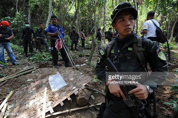 Soldiers stand guard as rescue workers and forensic officials dig out skeletons from shallow graves covered by bamboo at the site of a mass grave at...