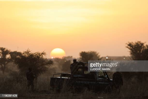 Soldiers stand guard at sunset as France's President and Niger's President Mahamadou Issoufou take part in a military ceremony at the Martyr Quarter...