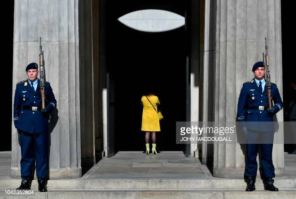 Soldiers stand guard at the Neue Wache memorial for the victims of war and dictatorship as a journalist looks inside ahead a wreath laying ceremony...