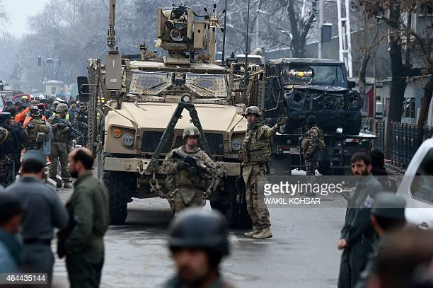 US soldiers stand guard at the scene of a suicide car bomb attack on a Turkish diplomatic vehicle in front of the Iranian embassy in Kabul on...