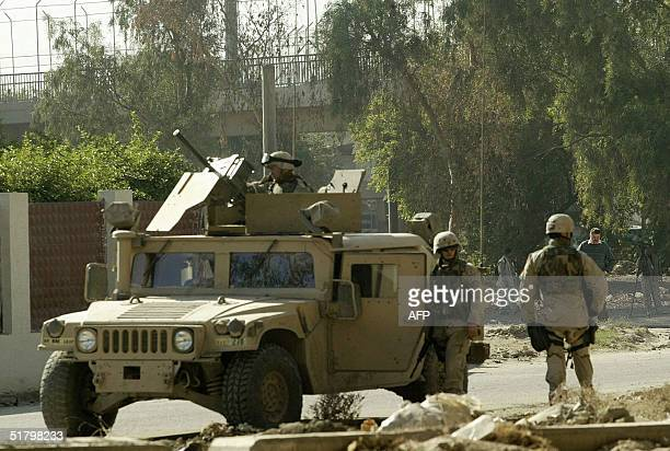 US soldiers stand guard at the site where a sport utility vehicle was damaged in a car bomb attack on the road leading to Baghdad international...