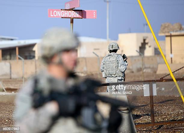 US soldiers stand guard at the Taji base complex which hosts Iraqi and US troops and is located thirty kilometres north of the capital Baghdad on...