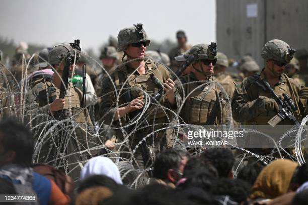 Soldiers stand guard behind barbed wire as Afghans sit on a roadside near the military part of the airport in Kabul on August 20 hoping to flee from...