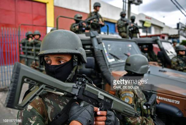 Soldiers stand guard during an operation to reduce thefts in cargos in Rio de Janeiro Brazil on September 11 2018 Security officials say the high...