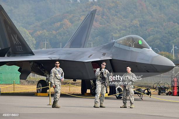 US soldiers stand guard in front of a F22 Raptor fighter jet on the tarmac during a media preview of the Seoul International Aerospace and Defense...
