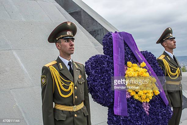 Soldiers stand guard in front of a floral wreath shaped like a forgetmenot which has become the symbol of Armenian genocide commemoration events at...