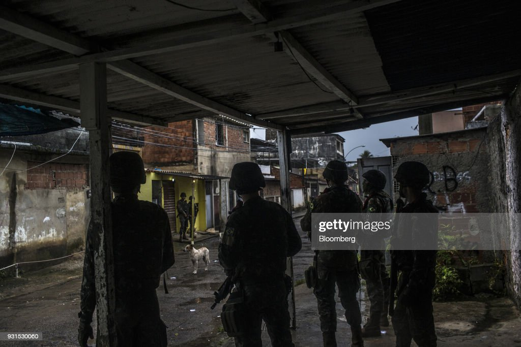 Soldiers stand guard in the Vila Kennedy neighborhood in Rio de Janeiro, Brazil, on Thursday, March 8, 2018. As public safety remains a top concern for Brazilian voters, President Michel Temer gave the military control of security measures in Rio in an effort increase approval ratings ahead of the country's elections in October. Photographer: Dado Galdieri/Bloomberg via Getty Images