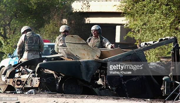 US soldiers stand guard near a burnt US Humvee vehicle September 21 2004 in Baghdad Iraq A car bomb exploded near a US military convoy damaging two...